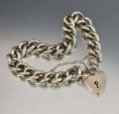 Superb English decorative engraved curb watch chain in sterling silver is clasped in the front with a charming heart padlock to form this stylized Victorian bra
