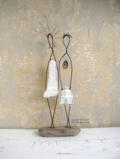 Beautiful rustic house decor! Wire sculpture titled Young Peace Couple. This beautiful mixed media driftwood and wire sculpture is made from recycled wire and mounted on a piece of driftwood. Perfect for those who love a rustic home decor and value the beauty of simplicity in life.  The female wire sculpture has copper earrings and a paper dress made from recycled paper from an old book. The guy has a ceramic peace sign around his neck and shorts made of recycled paper. The driftwood base…