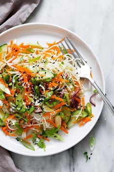 Spring Roll Noodle Salad - light, bright noodle salad packed with protein and vitamins and perfect for spring nights. Crisp carrots, scallion, red onion, cucumber and cilantro are served over a bed of rice noodles tossed with sesame seeds and a drizzle of honey-ginger vinaigrette.