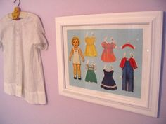 """Vintage paper dolls are so trendy right now -- and these pretty, teeny-tiny doll clothes make sweet decor. Plus, framing them couldn't be simpler.    What You'll Need: Retro paper dolls, an 11""""x14"""" frame and coloured paper sized to fit the frame.    How to DIY: Choose a paper doll and a selection of clothing to feature. Glue them to your coloured sheet of paper in a nice layout. Put it in the frame and hang it."""
