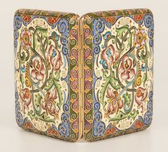 A Russian gilded silver and shaded cloisonné enamel cigarette case, attributed to Feodor Ruckert, Moscow, circa 1896-1908, both sides decorated with scrolling florals on a cream and olive green ground. Inscription on the interior dated 1914. Dimensions