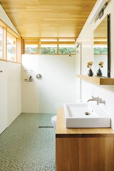 In the bathroom, a thin pane of glass separates the shower; an Aquaplane sink by Lacava hovers above a built-in vanity illuminated by a lean Adelphi light by Oxygen Lighting; and blue-green glass penny tiles by Terra Verre decorate the floor. The absence Bad Inspiration, Bathroom Inspiration, Built In Vanity, Penny Tile, Modern Bathroom Design, Modern Bathrooms, Small Bathrooms, Bathroom Designs, Bathroom Renos