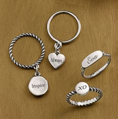Christmas Collection: Twisted Rope Dangle Ring shown with an engraved Tiny Engravable Charm, Stackable Dangle Ring shown with an engraved Puffed Heart Charm, Simple Signet Ring shown with engraving and Engravable Twisted Wire Ring shown with engraving #JamesAvery