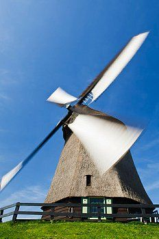 A windmill spinning in the wind, Holland, Netherlands.