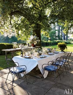These chairs!  On a terrace shaded by a linden tree, vintage wrought-iron chairs encircle a table set for an alfresco dinner; the striped cushions, tableware, and chandelier are by Ralph Lauren Home.