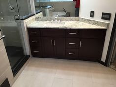 We used large gray porcelain tile with absolute black granite ledges and steps, custom espresso vanity and trim, upgraded frameless glass package with full pivot door. #bigbearremodeling