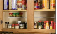 """Use a tension rod to create a """"second"""" shelf in your kitchen cabinets for spices."""