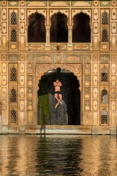 A young boy jumps from over 15/20m into a sacred pool dedicated to the morning baths e sun worshipping, being frozen in mid-air, levitating. Incredible India.