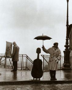 (Learn how to play the cello) A man on the sidewalk in rainy Paris. The man uses his umbrella to protect his cello case. This is the famous cellist Maurice Baquet. The image was taken by photographer Robert Doisneau in Robert Doisneau, Maurice Baquet, Rainy Paris, Street Photography, Art Photography, Musician Photography, Arte Black, Foto Poster, Glenn Close
