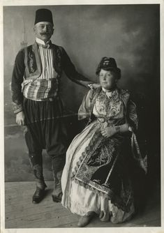 Aristocratic costumes, © The Historical Archive of Sarajevo. 1878-1916. Full-length shot of a couple in urban clothes with traditional elements. The man is wearing close-fitting trousers with a low, baggy crotch (čakšire), a short embroidered jacket (jelek), gaiters (dizlik) and a felt hat (fez). The woman is also wearing a felt hat (fez) and a woman´s oriental-style town costume.
