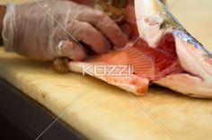 chef slicing fish. - Cropped close-up image if a chef slicing fish.