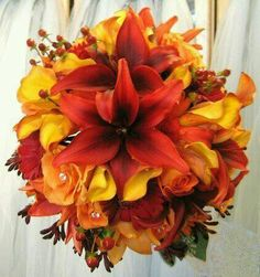Lillies, callas, mums, roses, hypericum, greens.  Gorgeous deep fall colors.  Add gerbs, possibly dahlias.