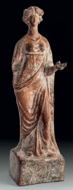 Large terracotta statuette depicting a young woman standing in swaying light. Great Greece, III / II century BC.