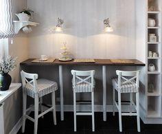 Przestrzeń między otwartymi półkami kuchennej zabudowy a ścianą zabudowano blatem wspartym na metalowych nogach, który tworzy prosty barek śniadaniowy. Ustawiono przy nim stylowe krzesła barowe, których pokrowce harmonizują z rzymską roletą w oknie. Tapeta w pasy nadaje ścianie subtelną fakturę.
