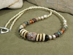 A primitive tribal southwestern necklace beaded with larger Picasso Czech beads, bone disc, amber horn rondelle, lots of metallic silver seed