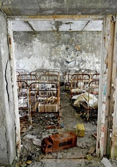 Cots in the former nursery in the abandoned town of Prypiat, Ukraine near the Chernobyl Nuclear Power Plant by Victoria Henry:
