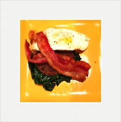 Burger over wilted spinach with fried egg and bacon