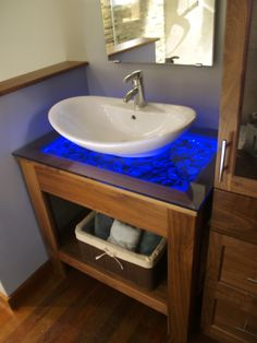 Blue lights illuminate the pebbles under the glass surface of this contemporary wood vanity. A vessel sink sits atop the glass surface, adding to the contemporary vibe of the space.