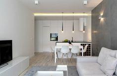aménagement salon salle à manger blanc et gris - cuisine blanche avec îlot central, table et chaises blanches, canapé blanc et mur imitation béton