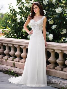 Sleeveless chiffon slim A-line gown with illusion bateau neckline, hand-beaded lace appliqué sweetheart bodice with asymmetrical waistline, illusion lace deep V-back, side split layered skirt with chapel train. Sizes: 0 – 20 Colors: Ivory, White