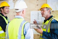 Stock Photo : Workers reading blueprints on site