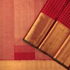 This classic kanjivaram sari in crimson red shot with ruby red is handwoven with checks in gold zari running along the body. The broad border has twill and paisley motifs in gold zari, with a selvedge in green.