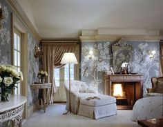The wallpaper here is an elegant touch, and it turns the room into a walled garden. All the panels were configured to fit the walls and then hand-painted. A Venetian mirror sits with Scandinavian pottery above the Louis XV fireplace. The demilunes are Louis XVI and the floor lamp is Bagues.