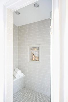 A glass door opens to a walk-in shower clad in light gray subway wall tiles fixed surrounding a tile framed niche covered in mini white hex tiles. 28 Inspirational Walk in Shower Tile Ideas for a Joyful Showering Tile Walk In Shower, Gray Shower Tile, White Subway Tile Bathroom, Subway Tile Showers, Grey Subway Tiles, Glass Tile Bathroom, Bath Shower, Glass Showers, Glass Subway Tile