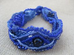 Beadwoven Bracelet in Blue This beautiful bracelet is done in a combination of Peyote and freeform netting stitches and contains a vintage Japanese glass bead as a focal