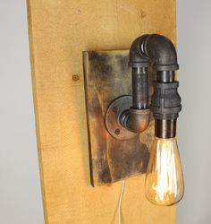 Black Pipe Wall Sconce Light kind of awesome. I would ditch the maple wood mounting or maybe paint it.