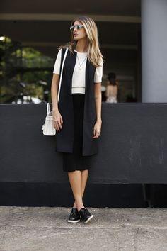 8 dicas para acertar na combinação com colete. t-Shirt branca, saia midi preta, terceira peça alongada, tênis preto