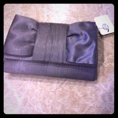 Jessica McClintock clutch/handbag NWT Has a strap that can be hid in the clutch. Very cute NWT silver/grey in color Jessica McClintock Bags Clutches & Wristlets