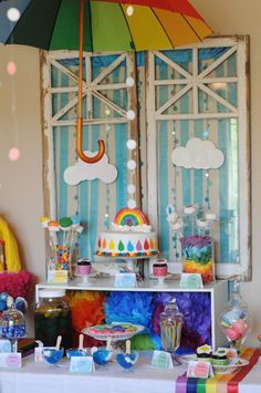"Very cute rainbow themed party decor! I love the old-window backdrop. I would pair it with a bright yellow paper pom for sunshine, and maybe hang raindrops from the umbrella instead of dots, but overall a cute theme. Maybe even for a baby ""shower""."