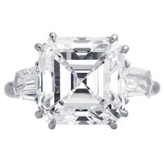 Harry Winston 8.02 Carat Asscher Cut Diamond Platinum Ring. Platinum 3 stone estate ring set with a stunning 8.02ct asscher cut diamond having a color and clarity of G-VS1, with GIA report #5121556626. The center diamond is flanked by two shield cut gem white diamonds totaling 1.5 carats, signed Harry Winston.