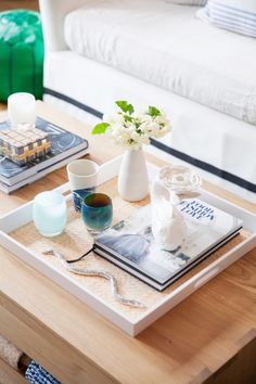 Light and bright coffee table trinkets: http://www.stylemepretty.com/living/2015/11/12/cocokelleys-bright-seattle-loft-tour/ Photography: Katie Parra - http://katieparra.com/