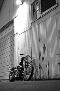 Motorcycle in dark alley.  At least he parked under the light.  Nice up-swept pipes.