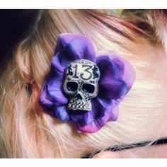This pretty flower hair clip is purple and features a black & white skull in the middle. Has a silver toned alligator hair clip securely fastened to the back and is approximately 2″ across. http://sinsnneedles.com