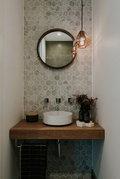 Maria opens the doors to her luxurious and contemporary home Stunning powder room with marble hexagon wall tiles, round mirror and copper pendant light As seen on season 1 of Decor Ideas That Make√ Small Bathroom Remo Powder Room Small, Wooden Vanity, Small Half Bathrooms, Round Mirror Bathroom, Small Bathroom, Hexagon Wall Tiles, Small Decor, Bathroom Decor, Bathroom Inspiration