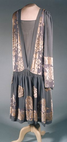 Dress, France or England, ca. 1929. Voided white silk velvet and blue silk georgette with applied velvet flowers. This attractive woven velvet is used in straight panels at the back, the stripes accentuating the tubular look. The velvet flowers have been cut out and applied to the front skirt.