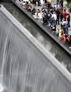 Family members gather at the edge of the North Pool during anniversary ceremonies at the World Trade Center site in New York on Sept. 11, 2011.
