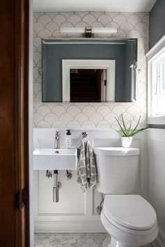 Keep up with tile trends. Fish scale tiles are a great way to update your kitchen or bathroom. Replace your subway tile with fish scale tile to stay on trend. For more design ideas and inspiration, go to Domino. Small Bathroom Ideas On A Budget, Small Half Bathrooms, Small Bathroom Colors, White Bathroom, Master Bathrooms, Tile Bathrooms, Bathroom Layout, Simple Bathroom, Comfort Room Tiles Small Bathrooms