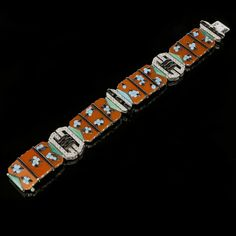 ART DECO MULTI GEM ENAMEL & DIAMOND BRACELET BY BOUCHERON c.1925.  Oriental inspiration set with 4 articulated jasper panels each with applied blue & black enamel blossom clusters between black enamel line borders joined by circular cut diamond geometric buckle design links with buff top triangular turquoise terminals.