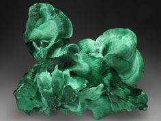 Malachite is a green, very common secondary copper mineral with a widely variable habit. Typically it is found as crystalline aggregates or crusts, often banded in appearence, like agates. It is also often found as botryoidal clusters of radiating crystals, and as mammillary aggregates as well. Single crystals and clusters of distinguishable crystals are uncommon, but when found they are typically acicular to prismatic.