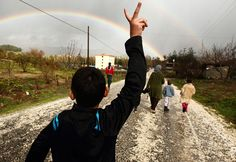 """Notice the rainbow. """"Hassan Saad, 13, who fled Idlib in Syria, flashes a victory sign while walking outside the refugees camp near the Turkish-Syrian border in the southeastern city of Yayladagi, on February 16, 2012. Hassan said that his father was killed by the pro-Syrian President Bashar Al-Assad army five months ago. (Reuters/Zohra Bensemra)"""""""