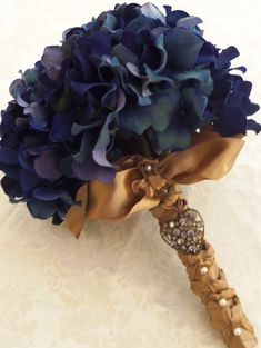 Blue Hydrangeas as wedding bouquet, with the handle decorated and covered with gold