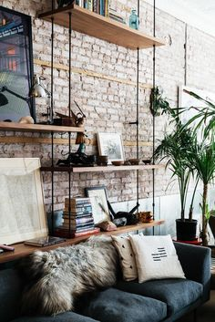 Tijolos aparentes podem reduzir o custo da reforma, trazer um ar industrial ao apartamento, ou deixar os ambientes com um estilo naked. Aqui, a parede foi coberta com prateleiras, que expõem livros, quadros, luminária e outros itens de decoração.