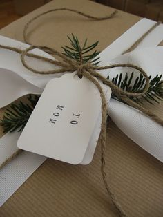 Brown wrapping, white ribbon, pine sprig and a simple tag.