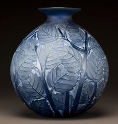 R. LALIQUE BLUE GLASS MILAN VASE WITH WHITE PATINA Circa 1929. Molded R. LALIQUE