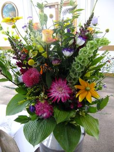One of a pair of milk churn arrangements containing bright and colourful cottage garden flowers