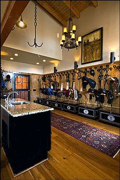 This is a nice design for a tack room. Lots of bridle hooks to hang bridles properly, the saddles are in nice order, and trunks to keep any extra tack and supplies out of the way. I also like the sink/island for preparing horses food, washing up, etc.